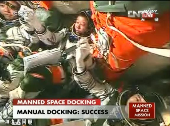 The three astronauts aboard China's Shenzhou 9 spacecraft grasp hands to celebrate their successful manned docking with the Tiangong 1 orbiting module on June 24, 2012, in this still from a state CCTV broadcast. At center is astronaut Liu Wang,