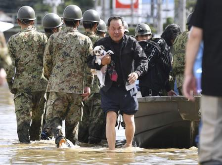 A local resident carrying his pet dog evacuates from an area flooded by the Abukuma river following Typhoon Hagibis in Motomiya