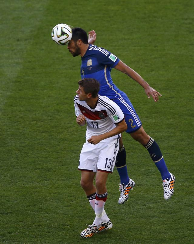 Germany's Thomas Mueller and Argentina's Ezequiel Garay (top) fight for the ball during their 2014 World Cup final at the Maracana stadium in Rio de Janeiro July 13, 2014. REUTERS/Ricardo Moraes (BRAZIL - Tags: SOCCER SPORT WORLD CUP)
