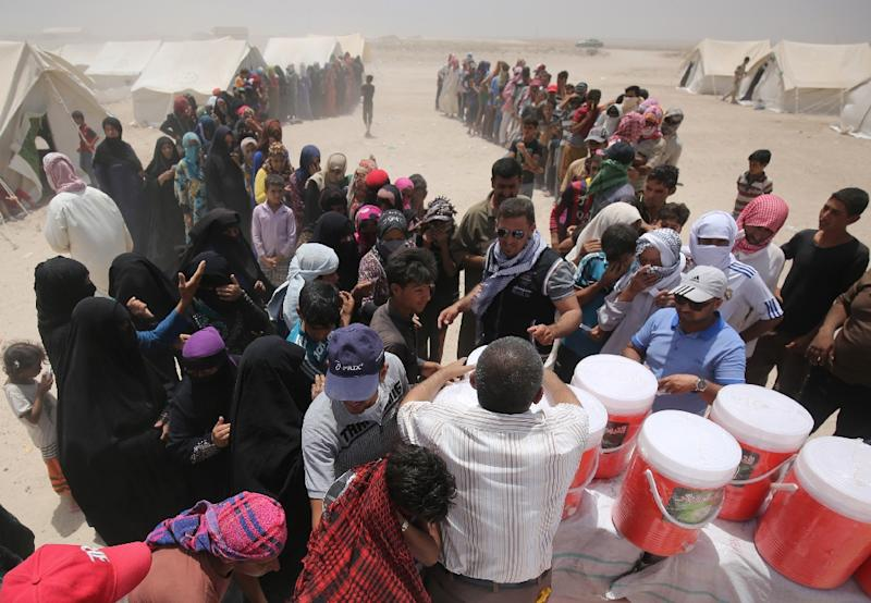 Iraqi displaced from the city of Fallujah queue up to collect aid distributed by the Norwegian Refugee Council at a newly opened camp where they are taking shelter in Amriyat al-Fallujah on June 27, 2016 (AFP Photo/Ahmad Al-Rubaye)
