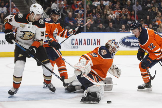 Anaheim Ducks' Derek Grant (38) and Andrej Sekera (2) look for a rebound as Edmonton Oilers goalie Mikko Koskinen (19) makes the save during the third period of an NHL hockey game Saturday, Feb. 23, 2019, in Edmonton, Alberta. (Jason Franson/The Canadian Press via AP)