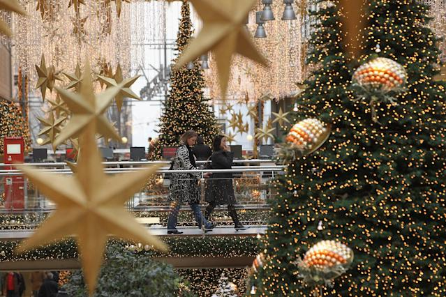 People walk among Christmas trees and decorations in the Potsdamer Platz Arkaden shopping mall on November 30, 2011 in Berlin, Germany. (Photo by Sean Gallup/Getty Images)
