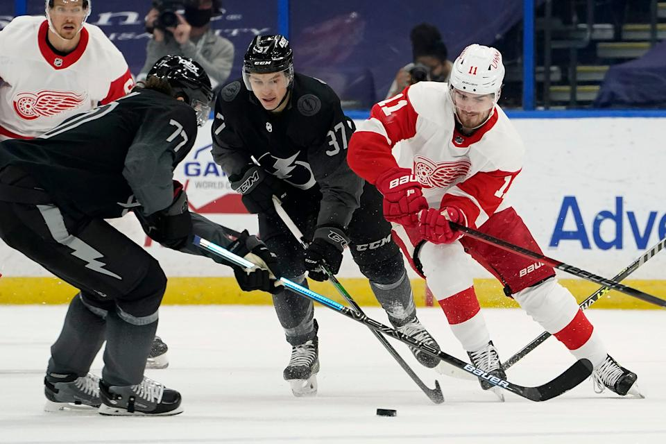 Detroit Red Wings right wing Filip Zadina (11) works the puck away from Tampa Bay Lightning center Yanni Gourde (37) and defenseman Victor Hedman (77) during the first period of an NHL hockey game Saturday, April 3, 2021, in Tampa, Fla.