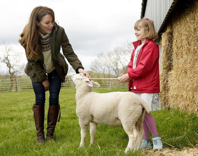 The Duchess of Cambridge strokes a lamb with farmer's daughter Clover Chapman