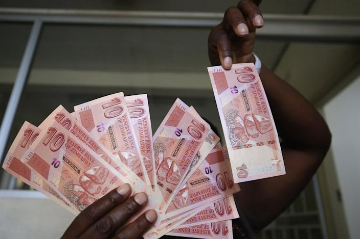 On Wednesday, a woman holds newly created bank notes in the Zimbabwe capital, Harare, put into circulation to ease the cash crisis.