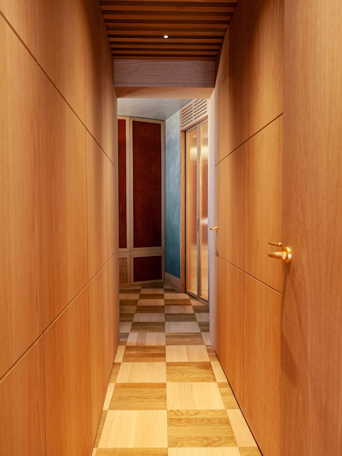 """<div class=""""caption""""> Adorned with wood from floor to ceiling, the corridor leads to the master bedroom. </div>"""
