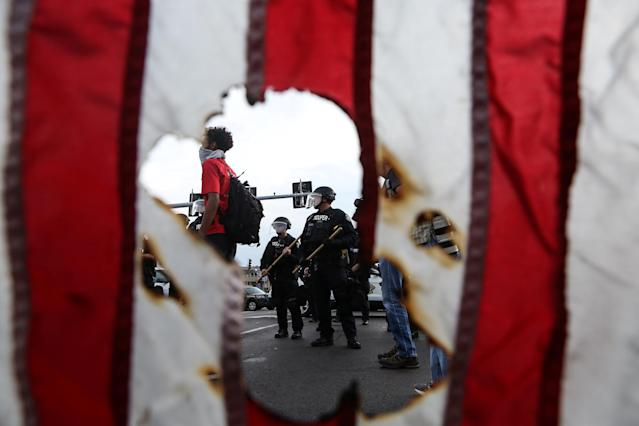 <p>Police in riot gear and a protester stand near a burned U.S. flag after the not guilty verdict in the murder trial of Jason Stockley, a former St. Louis police officer charged with the 2011 shooting of Anthony Lamar Smith, in St. Louis, Mo., Sept. 17, 2017. (Photo: Lawrence Bryant/Reuters) </p>