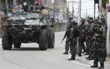 An armoured vehicle drives past government soldiers for another offensive against the Muslim rebels of Moro National Liberation Front (MNLF) positions in Zamboanga city in southern Philippines September 16, 2013. REUTERS/Erik De Castro