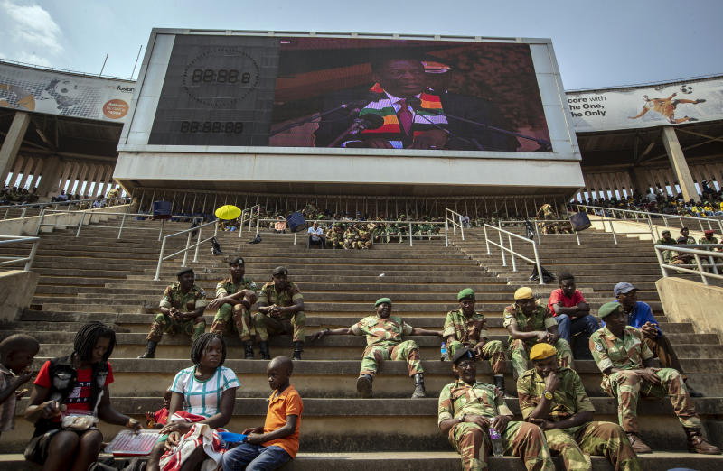 Members of the military sit in the stands as Zimbabwe's President Emmerson Mnangagwa is seen on a video screen above, during the state funeral for former president Robert Mugabe at the National Sports Stadium in the capital Harare, Zimbabwe Saturday, Sept. 14, 2019. African heads of state and envoys gathered to attend a state funeral for Zimbabwe's founding president, Robert Mugabe, whose burial has been delayed for at least a month until a special mausoleum can be built for his remains. (AP Photo/Ben Curtis)
