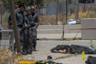Israeli forces inspect the scene of a shooting attack where bodies of two Palestinian gunmen, killed by Israeli border police, lie on the ground in front of the military base of Salem near the West Bank town of Jenin, Friday, May. 7, 2021. Israeli troops shot and killed the two men and wounded a third after they opened fire on a border police base in the occupied West Bank. It was the latest in a series of violent confrontations amid soaring tensions in Jerusalem. (AP Photo/Gil Eliyahu)
