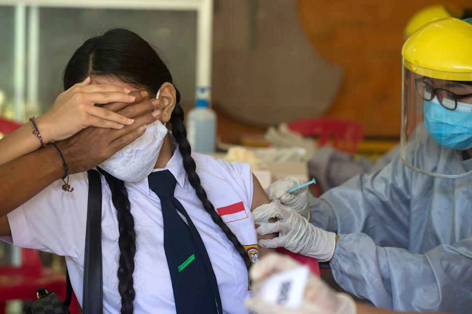 A teenager receives a shot of the Sinovac vaccine in Bali, Indonesia, on 5 July (Copyright 2021 The Associated Press. All rights reserved.)