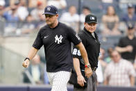 New York Yankees manager Aaron Boone, left, walks off the field after being ejected by umpire Sean Barber (29) in the ninth inning of a baseball game against the Oakland Athletics, Saturday, June 19, 2021, in New York. (AP Photo/John Minchillo)