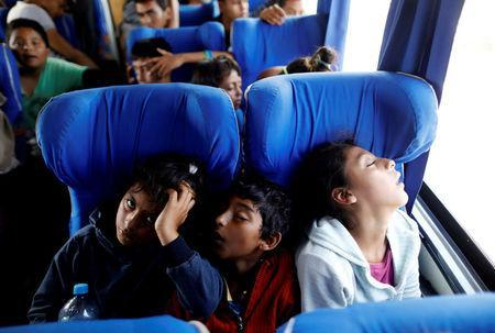 Children sleep while riding on a bus with fellow Central American migrants, as part of a caravan moving through Mexico toward the U.S. border, on a highway in Puebla state, Mexico April 6, 2018. REUTERS/Edgard Garrido