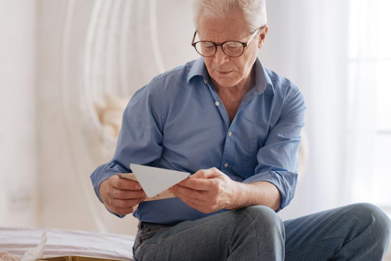 A seated senior man looks down at an envelope in his hands.