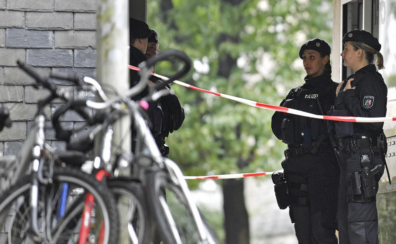 Police secure the entrance of a house where five dead children were found in Solingen, Germany, Thursday, Sept. 3, 2020. Police say the five children have been found dead at an apartment in the western German city, and their mother is suspected of killing them. (AP Photo/Martin Meissner)