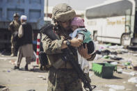 In this image provided by the U.S. Marine Corps, a Marine with the 24th Marine Expeditionary Unit (MEU) carries a baby as the family processes through the evacuation control center at Hamid Karzai International Airport in Kabul, Afghanistan, Saturday, Aug. 28, 2021. (Staff Sgt. Victor Mancilla/U.S. Marine Corps via AP)