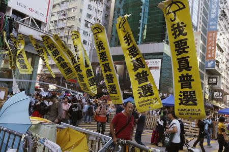 Passers-by walk in between barricades set up by pro-democracy protesters blocking a main road at Mong Kok shopping district in Hong Kong, November 24, 2014. REUTERS/Bobby Yip