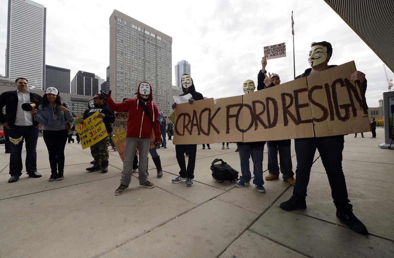 "Demonstrators hold up signs outside Toronto City Hall November 5, 2013. Toronto Mayor Rob Ford admitted Tuesday that he has smoked crack cocaine, probably ""in one of my drunken stupors"", but insisted he's not an addict. REUTERS/Aaron Harris (CANADA - Tags: CRIME LAW POLITICS)"