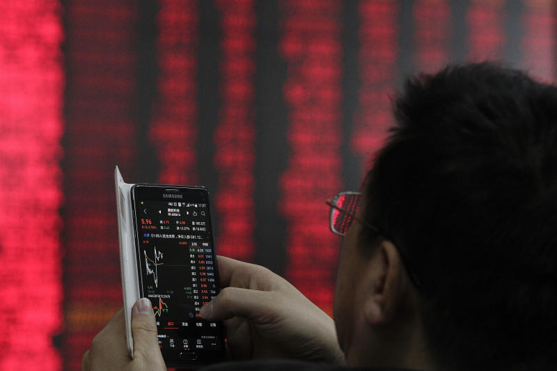 A man checks stock prices through his smartphone at a brokerage house in Beijing, Wednesday, Jan. 9, 2019. Shares extended gains in Asia on hopes for progress in resolving the tariffs battle between the U.S. and China as talks appeared to have been extended in Beijing. (AP Photo/Andy Wong)