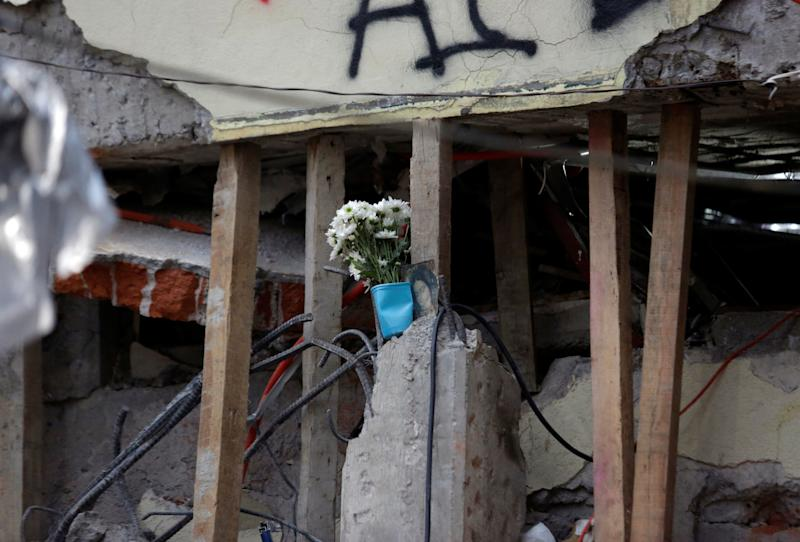 Flowers and a religious image are seen amidst support beams and rubble during the search for students.