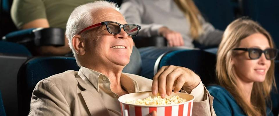 Good old movies. Cheerful senior man wearing 3D glasses grabbing popcorn while enjoying a movie with his family at the cinema copyspace seniority happiness industry fun leisure concept