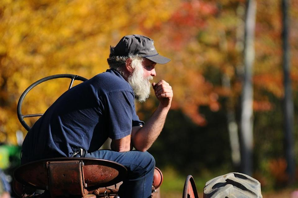 A New Hampshire farmer sits on his tractor