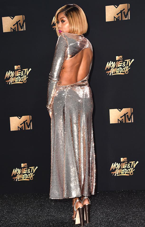 <p>glitters from all angles in her cutout sequin rose gold Emilio Pucci gown paired with matching metallic platform sandals and a fuschia lip.</p>