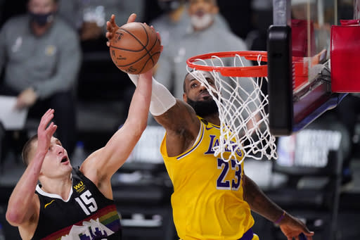 Denver Nuggets' Nikola Jokic (15) and Los Angeles Lakers' LeBron James (23) reach for a rebound during the first half of an NBA conference final playoff basketball game Thursday, Sept. 24, 2020, in Lake Buena Vista, Fla. (AP Photo/Mark J. Terrill)