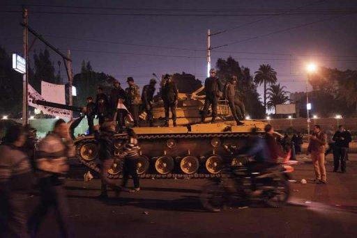 <p>Egyptian soldiers stand on top of a tank as opposition supporters pass by during a demonstration against President Mohammed Morsi outside the presidential palace December 9,in Cairo. Rival mass protests have been called for next Tuesday in Egypt over a bitterly disputed constitutional referendum, raising the potential for more violent street clashes in a sharpening political crisis.</p>