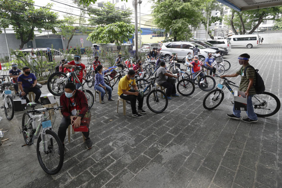 Recipients of bicycles from the Benjamin Canlas Courage to be Kind Foundation gather outside a building at the financial district of Manila, Philippines, Saturday, July 11, 2020. Restricted public transportation during the lockdown left many Filipinos walking for hours just to reach their jobs. A foundation saw the need and gave away mountain bikes to nominated individuals who are struggling to hold on to their jobs in a country hard hit by the coronavirus. (AP Photo/Aaron Favila)