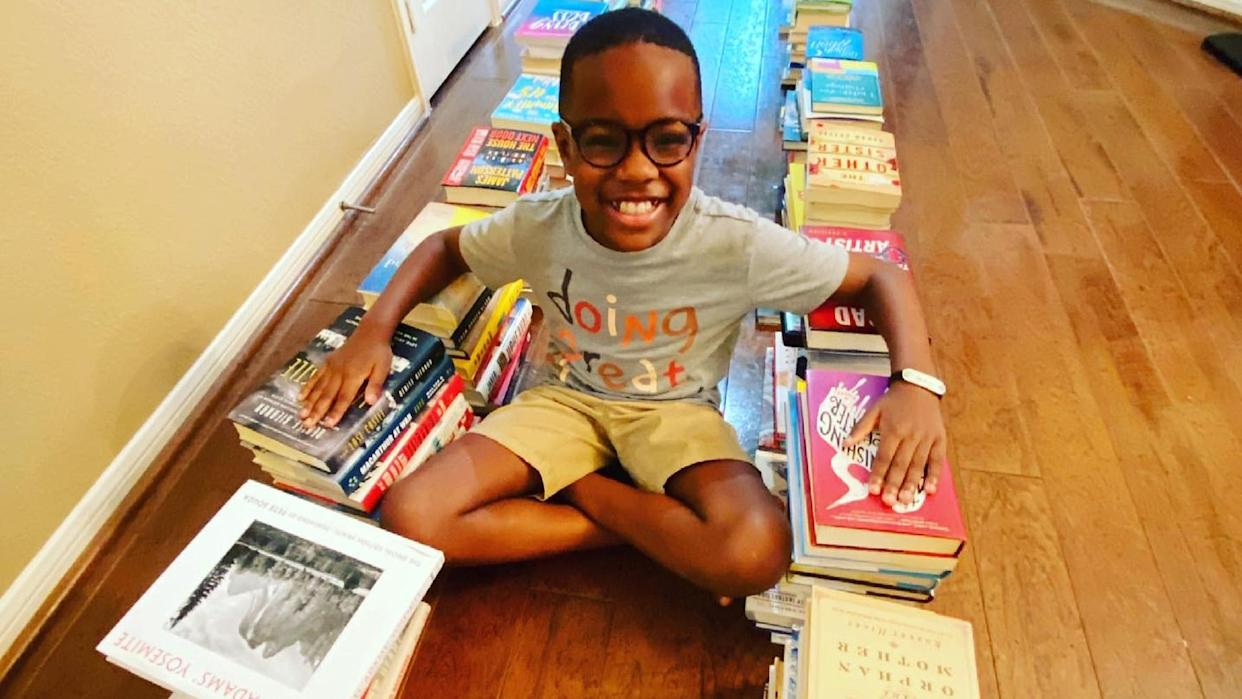 Orion smiles while seated cross-legged on the floor between two rows of books.