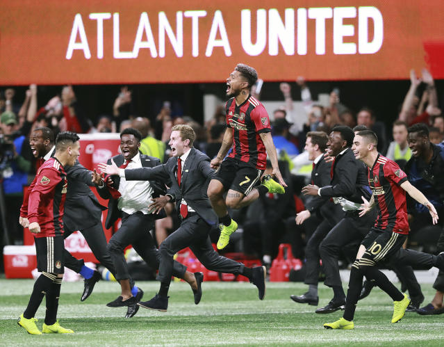 Atlanta United's Josef Martinez (7) leaps in the air and Miguel Almiron (10) charges the field celebrating their 2-0 defeat of the Portland Timbers in the MLS Cup championship soccer game, Saturday, Dec. 8, 2018, in Atlanta. (Curtis Compton/Atlanta Journal-Constitution via AP)