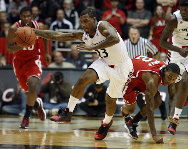 Cincinnati guard Sean Kilpatrick (23) gains control of the ball against North Carolina State guard Anthony Barber (2) during the first half of an NCAA college basketball game Tuesday, Nov. 12, 2013, in Cincinnati. (AP Photo/David Kohl)