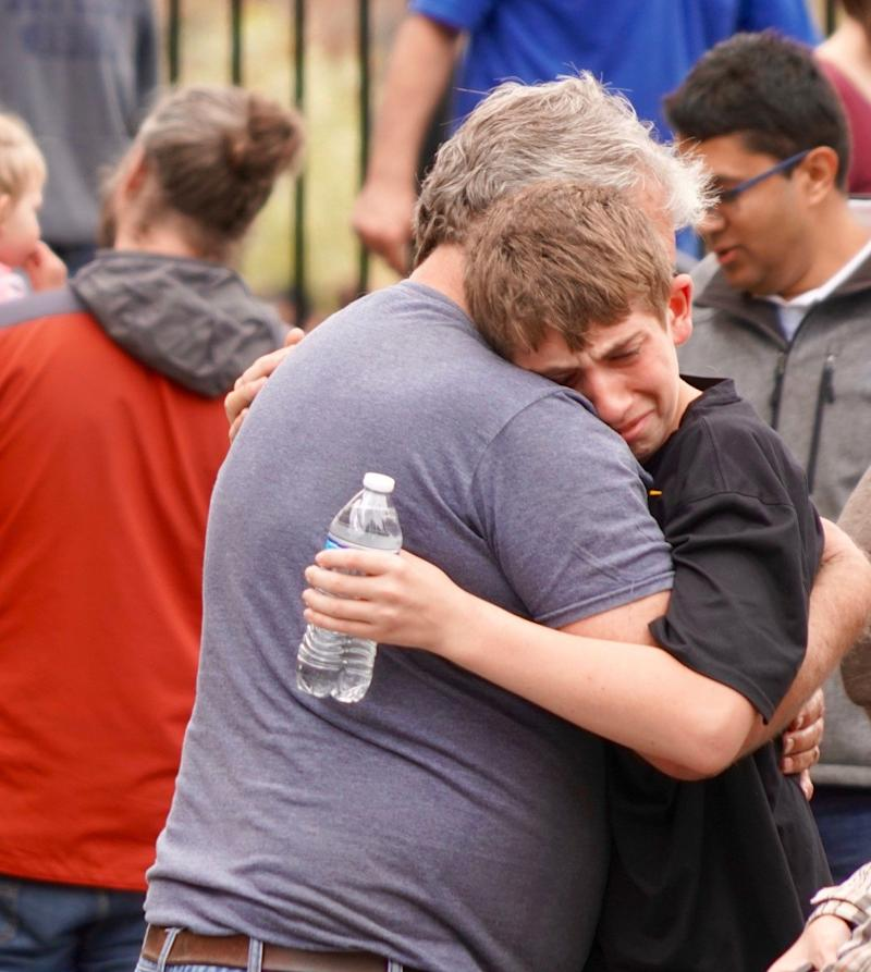 Robert Helfer, 13, hugs his grandfather, Shawn Helfer, 57, following a school shooting near Denver on Tuesday.