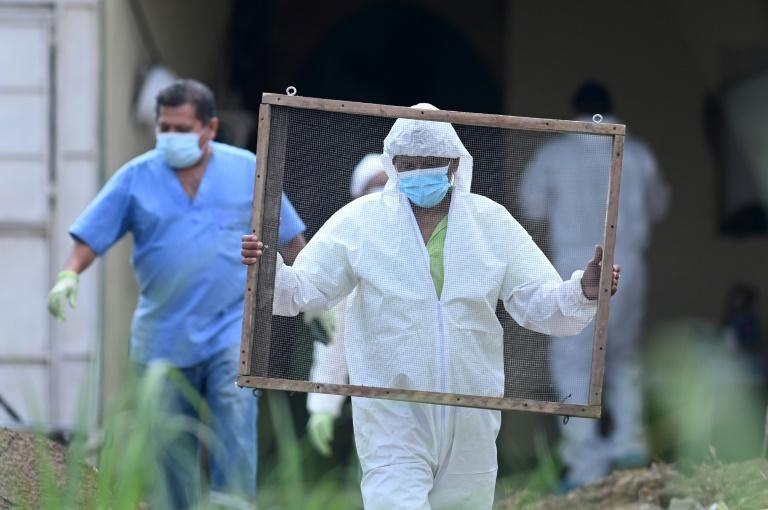 Clad in full biosafety gear, a team entered the home of ex-cop Hugo Ernesto Osorio Chavez, suspected of killing more than a dozen people