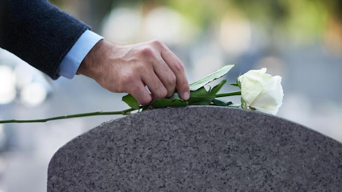 Cropped shot of a man placing a white rose on a grave.