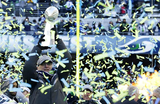 Seattle Seahawks owner Paul Allen lifts the Vince Lombardi Trophy during a rally on Wednesday, Feb. 5, 2014, in Seattle. The Seahawks defeated the Denver Broncos on Sunday in NFL football's Super Bowl XLVIII game in East Rutherford, N.J. (AP Photo/Ted S. Warren)