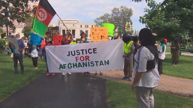 People carry a banner reading 'Justice for Afghanistan' as they march through the Peace and Friendship Park in Halifax on Aug. 25, 2021.  (Dave Laughlin/CBC - image credit)