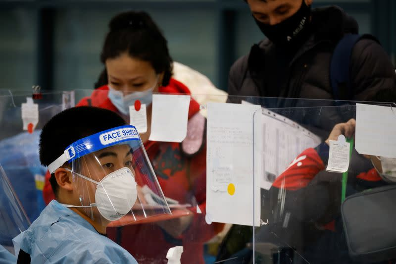 A worker wearing protective gear checks passengers from overseas as they arrive at the Incheon International Airport, in Incheon