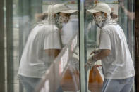 A delivery courier wearing a face mask to protect against COVID-19 is reflected in a window glass as she walks into a restaurant in Beijing, Tuesday, July 27, 2021. (AP Photo/Mark Schiefelbein)