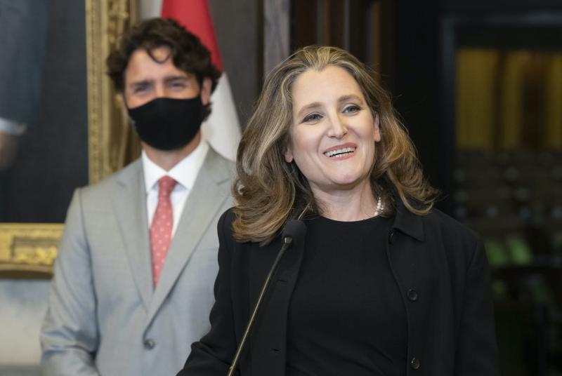 Chrystia Freeland speaks at a news conference with Justin Trudeau behind her, wearing a mask.