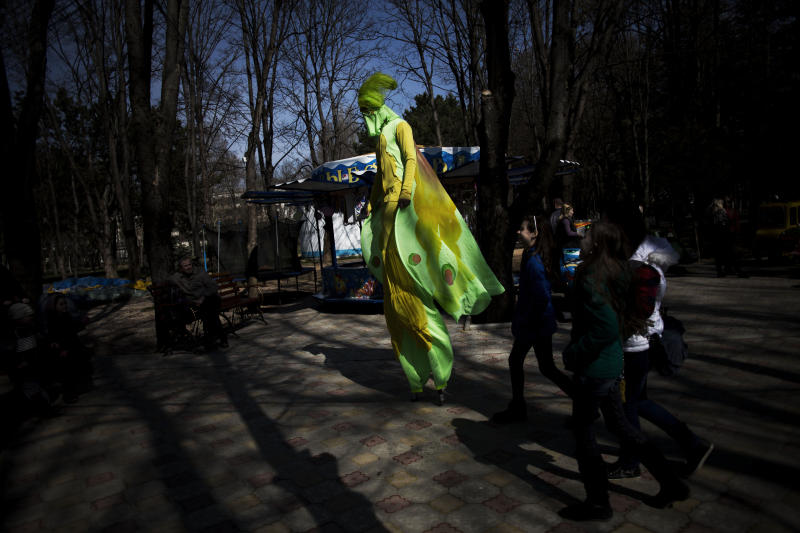 A Ukrainian man on stilts walks in a park in Simferopol, Ukraine, Friday, March 15, 2014. Tensions are high in the Black Sea peninsula of Crimea, where a referendum is to be held Sunday on whether to split off from Ukraine and seek annexation by Russia. (AP Photo/Manu Brabo)