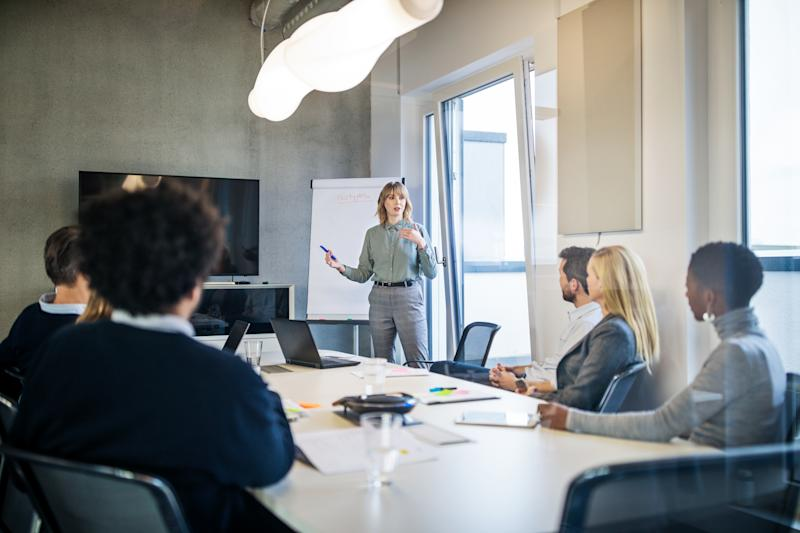 Businesswoman addressing a meeting around board table. Group of business people having board meeting in modern office.
