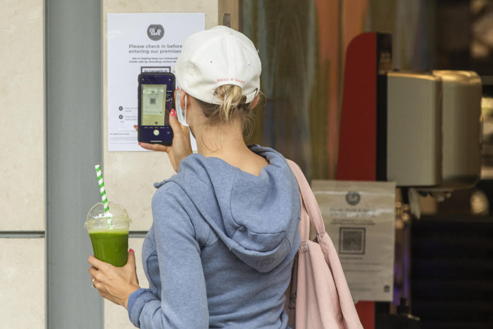 A woman holding a drink and wearing a mask scans a QR code on her phone. Source: Getty Images