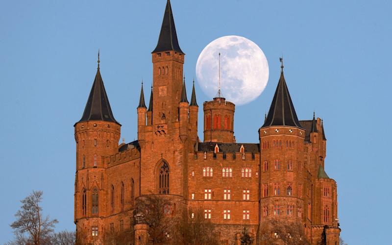 The full moon rise above Hohenzollern castle in Hechingen, Germany - SHUTTERSTOCK