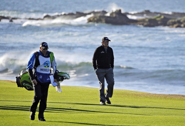 FILE - In this Feb. 11, 2019, file photo Phil Mickelson walks up the 18th fairway of the Pebble Beach Golf Links with his brother and caddie Tim Mickelson during the final round of the AT&T Pebble Beach Pro-Am golf tournament in Pebble Beach, Calif. At Pebble Beach, a course teeming with history for Mickelson, the 48-year-old, five-time major champion will come face to face with what might be his last, best chance to win the U.S. Open and become the sixth player to complete the career Grand Slam. (AP Photo/Eric Risberg, File)