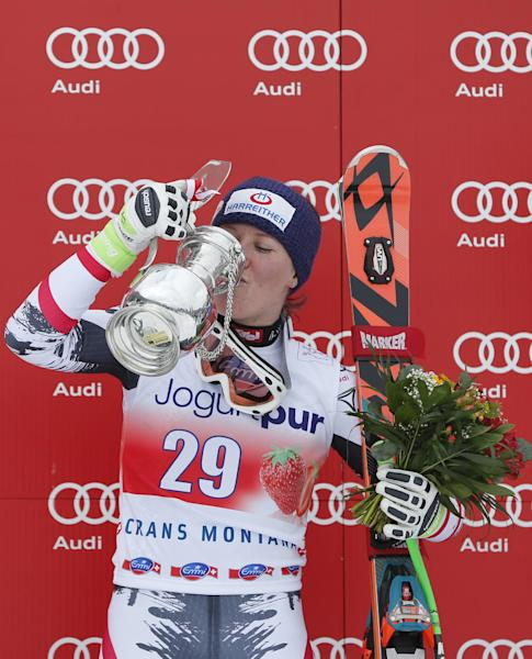 Austria's Andrea Fischbacher celebrates with her trophy on the podium after winning an alpine ski, World Cup women's downhill, in Crans Montana, Switzerland, Sunday, March 2, 2014. (AP Photo/Marco Trovati)