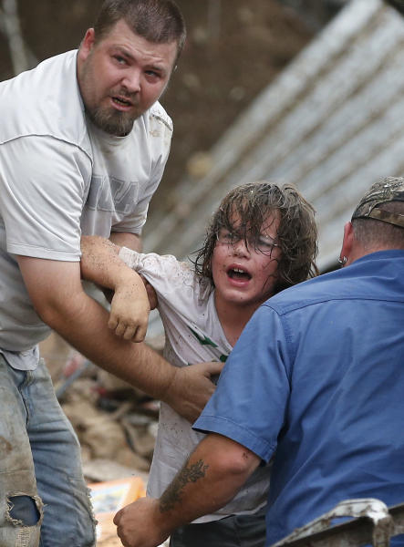 A child calls to his father after being pulled from the rubble of the Tower Plaza Elementary School following a tornado in Moore, Okla., Monday, May 20, 2013. A tornado as much as half a mile (.8 kilometers) wide with winds up to 200 mph (320 kph) roared through the Oklahoma City suburbs Monday, flattening entire neighborhoods, setting buildings on fire and landing a direct blow on an elementary school. (AP Photo Sue Ogrocki)