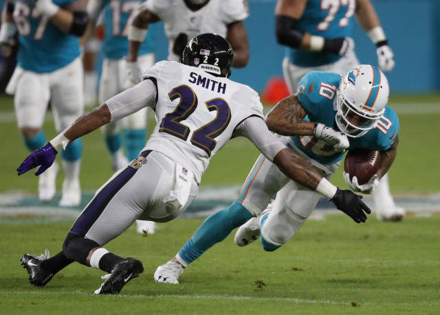 Miami Dolphins wide receiver Kenny Stills (10) attempts to avoid Baltimore Ravens defensive back Jimmy Smith (22) during the first half of a preseason NFL football game, Saturday, Aug. 25, 2018, in Miami Gardens, Fla. (AP Photo/Brynn Anderson)