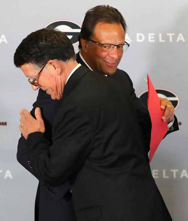 Georgia's new men's basketball coach Tom Crean, right, gets a hug from athletics director Greg McGarity during an NCAA college basketball news conference, Friday, March 16, 2018, at Stegeman Coliseum in Athens, Ga. (Curtis Compton/Atlanta Journal-Constitution via AP)